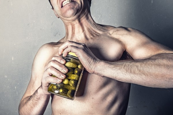 shirtless-man-trying-to-open-jar-with-pickles